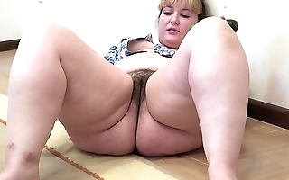 A chubby chick anent a soft pussy masturbates anent a cucumber